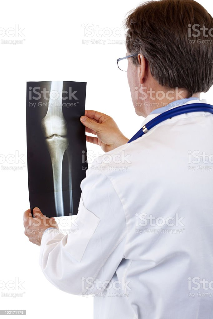 Backside of senior male doctor looking at radiograph x-ray image royalty-free stock photo