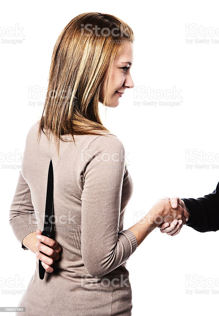 Backstabbing! Insincerely smiling blonde shakes hands with dagger behind back stock photo