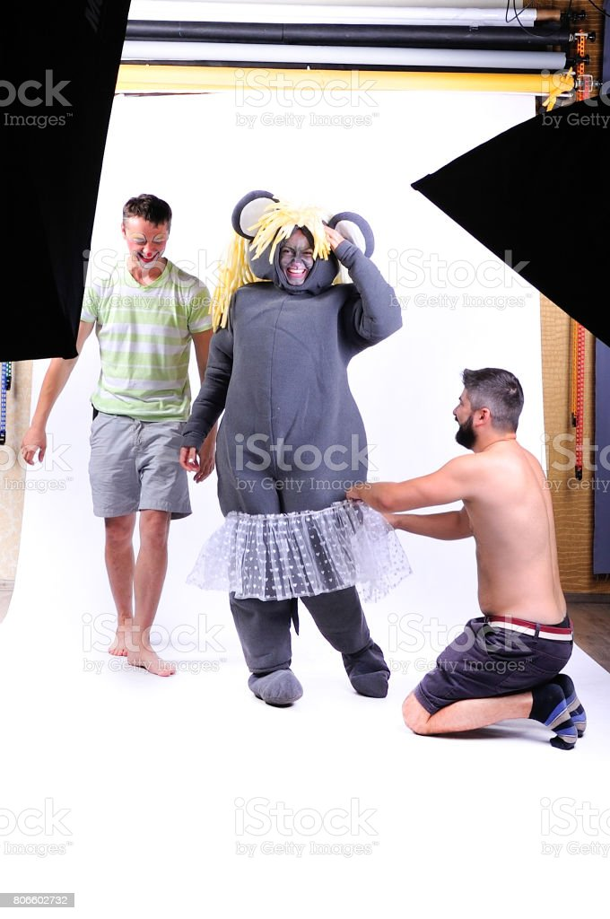 Backstage: smiling and fooling around animator in theater role - a grey mouse - and two men helping her to dress up stock photo