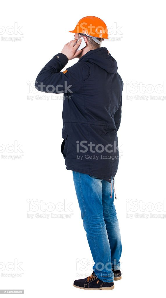 Backview of an engineer in construction helmet stands and using stock photo