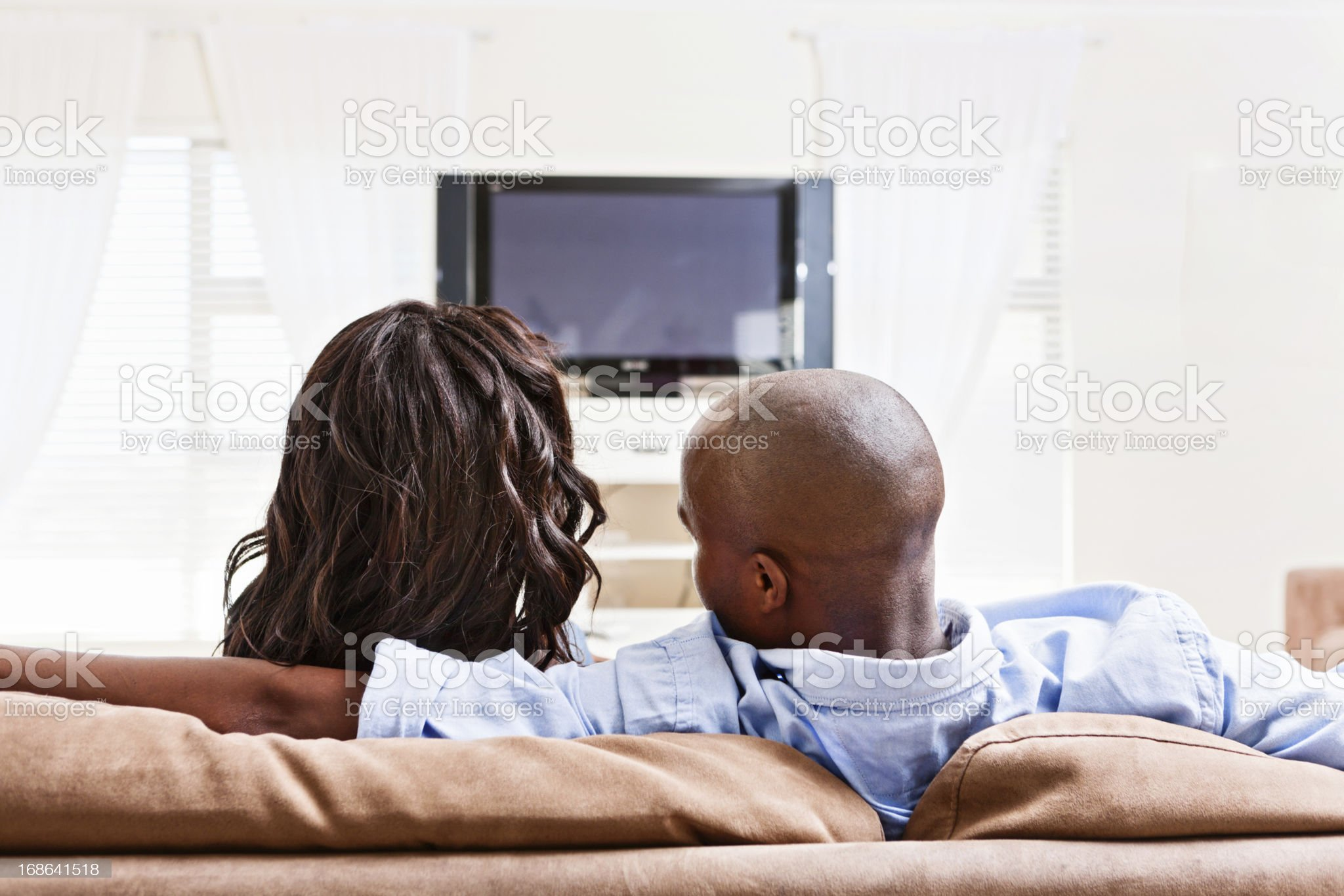 Backview of couple watching TV: he sneaks a hug royalty-free stock photo