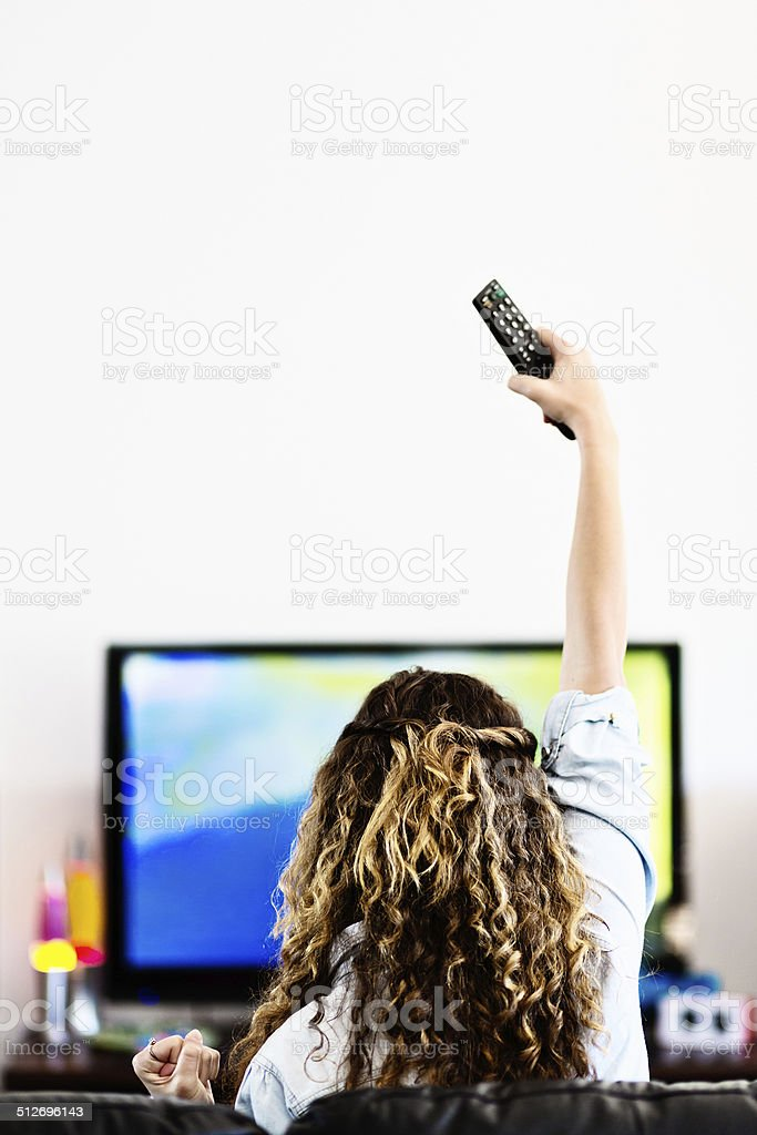 Backview of curly-haired woman waving TV remote triumphantly stock photo