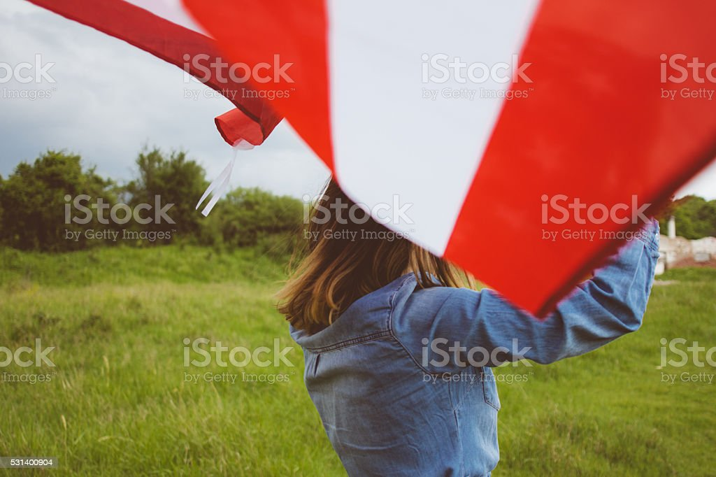 Backview of jolly girl running over meadow with U.S. flag stock photo