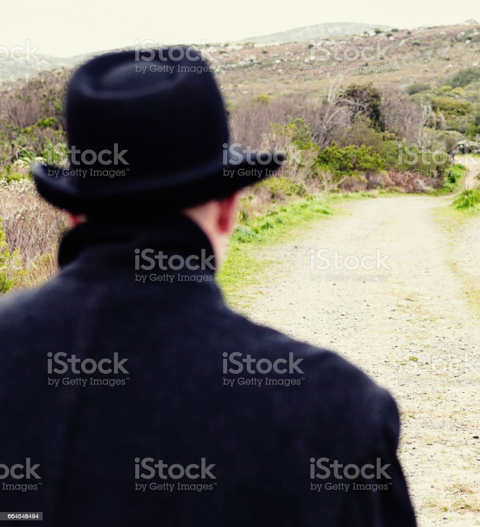Backview of man in overcoat and hat on country road stock photo