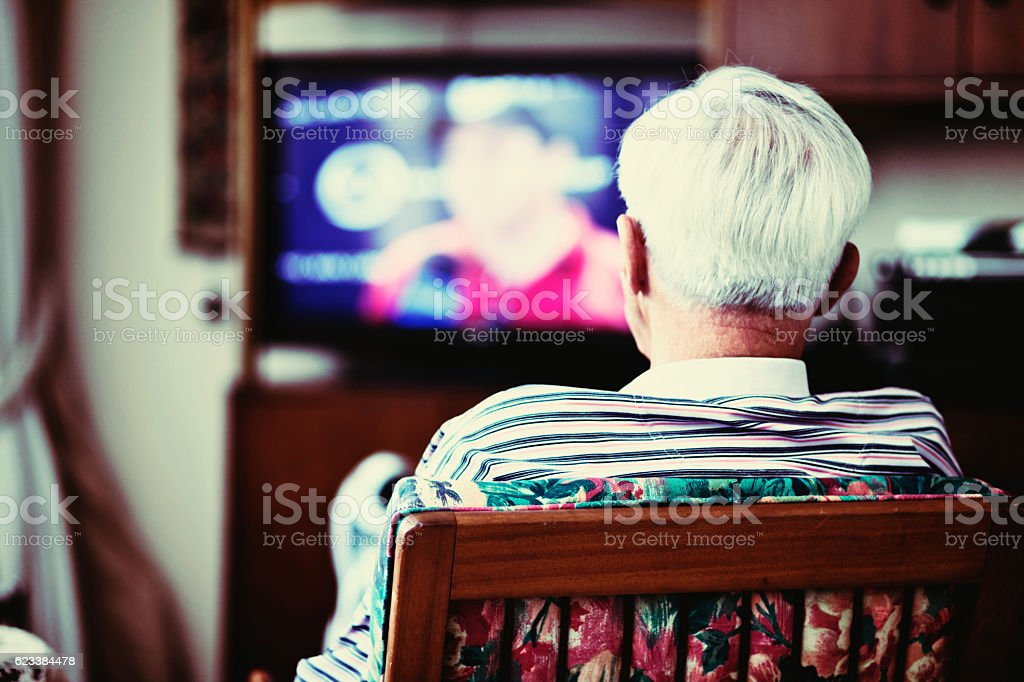 Backview of solitary very old man watching TV stock photo
