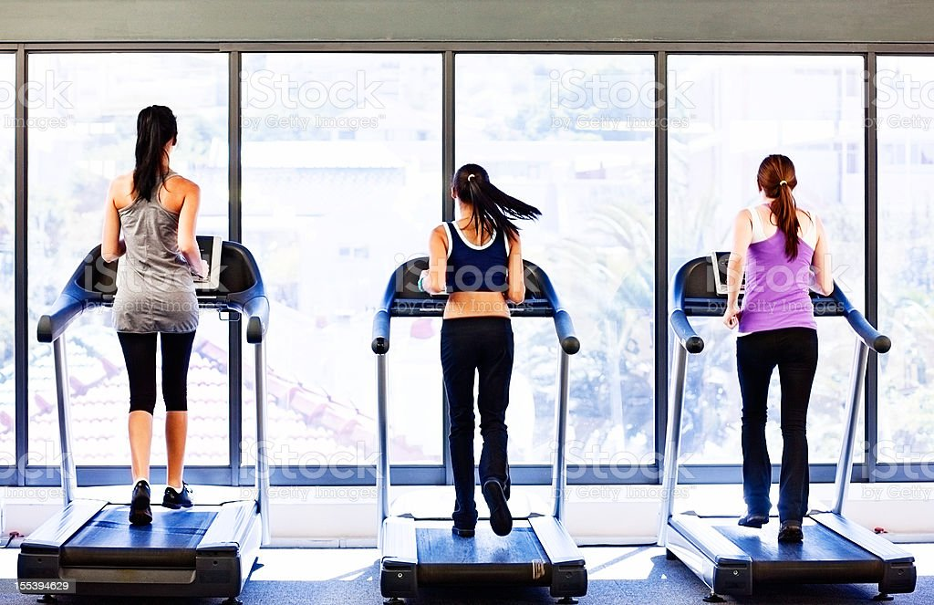 Backview of three young women using treadmills in gym stock photo