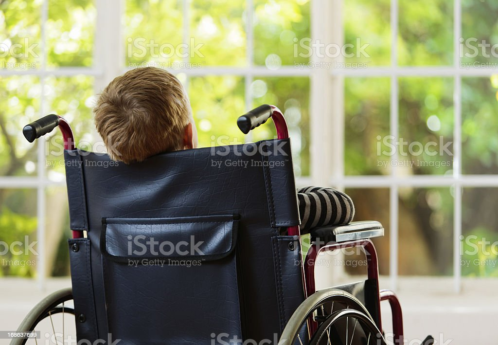 Backview of wheelchair-bound boy watching garden he cannot play in stock photo