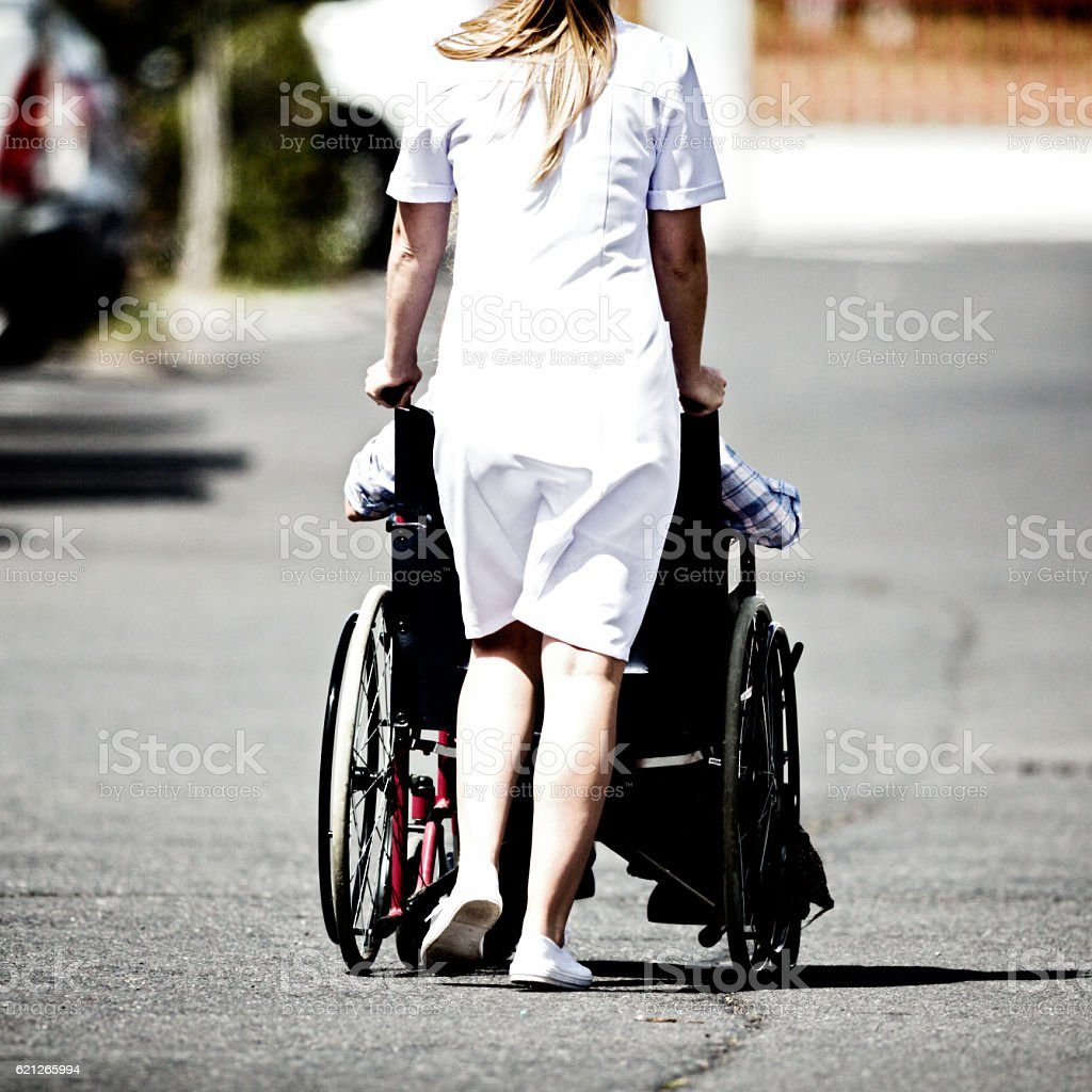 Backview of young nurse pushing patient through parking lot stock photo