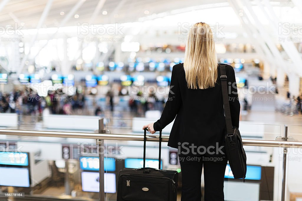 Backview of young woman looking toward airport check-in counters royalty-free stock photo
