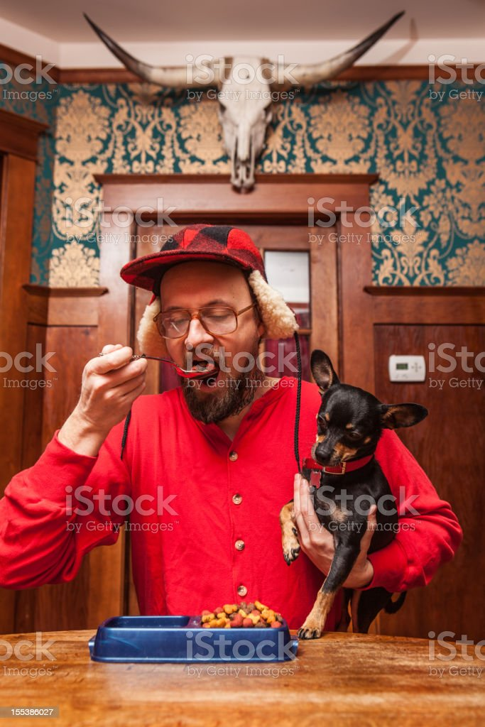 Backwoods Man Eats his Dog's Kibble at Kitchen Table 1 stock photo