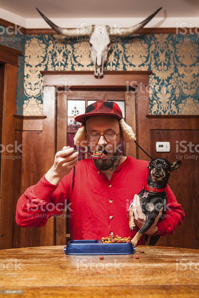 Backwoods Man Eats his Dog's Kibble at Kitchen Table stock photo