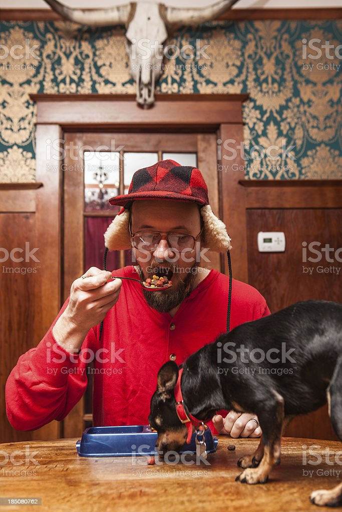 Backwoods Man Eats Kibble at Kitchen Table with his Dog stock photo