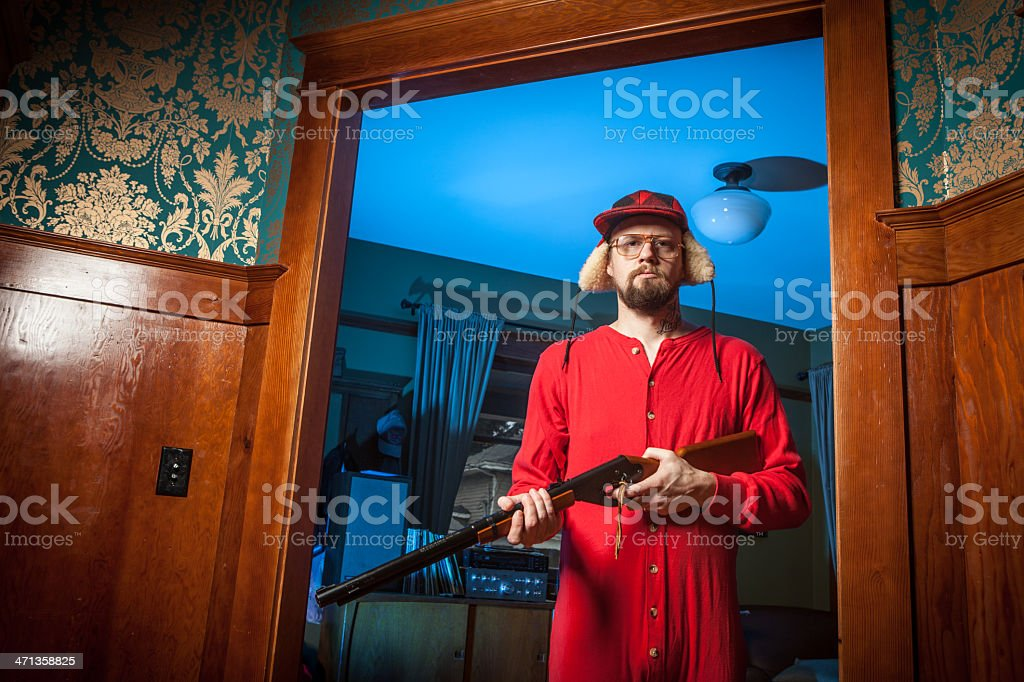 Backwoods Man in Doorway with Shotgun Wearing Long Underwear stock photo