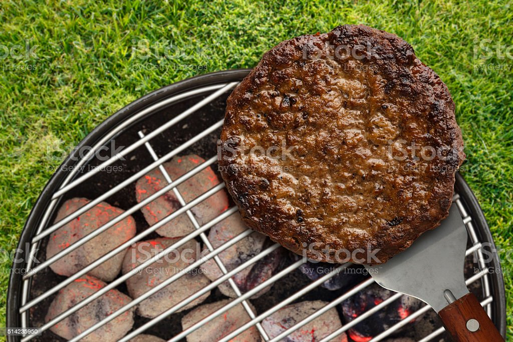 Backyard Cookout with Hamburger on Spatula Outdoors stock photo