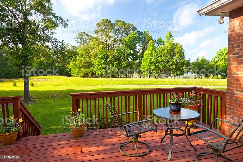 Backyard deck with large green yard stock photo