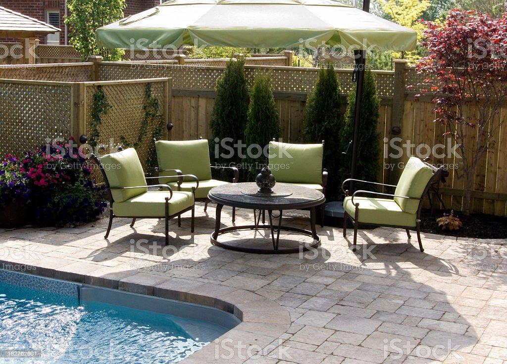 Backyard furniture next to an inground pool stock photo