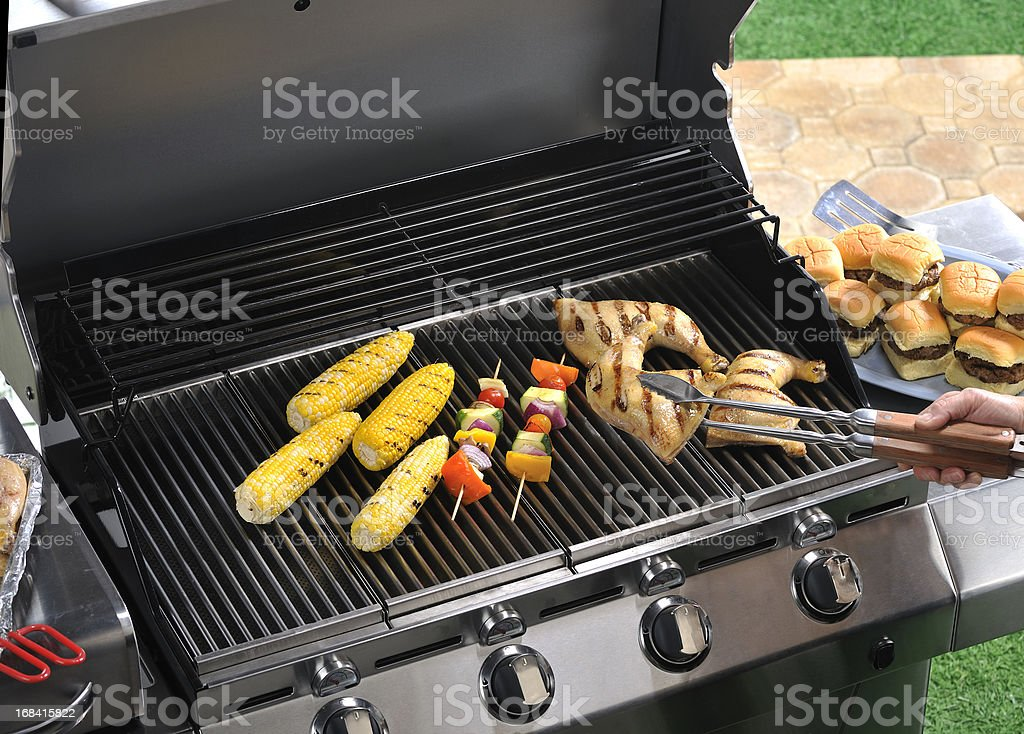 Backyard grilling scene with bbq kabobs, corn and chicken stock photo