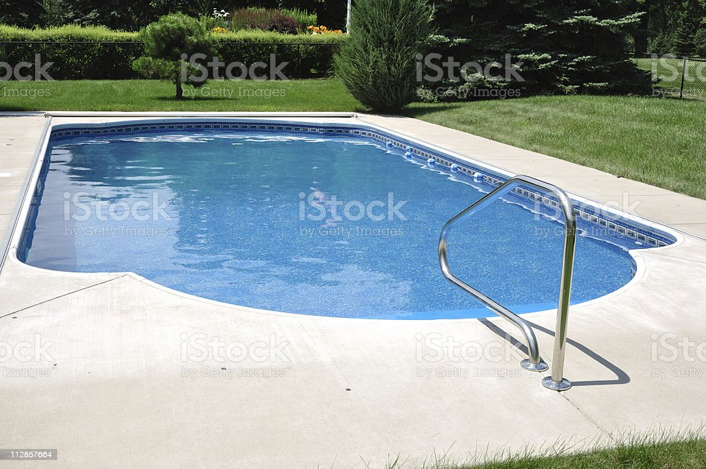 Backyard In-Ground Swimming Pool on sunny day royalty-free stock photo