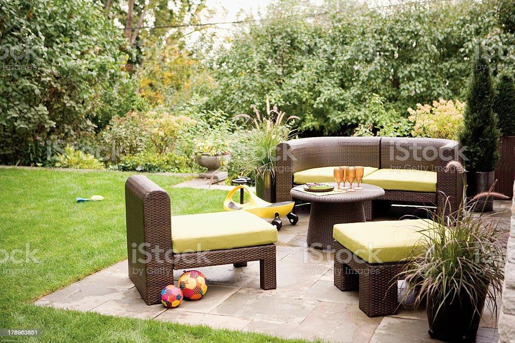 Backyard patio with furniture and greenery stock photo