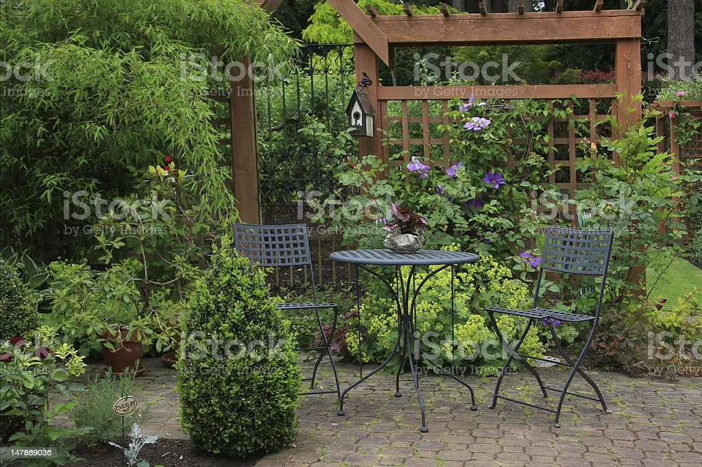 Backyard patio with rich foliage and furniture stock photo