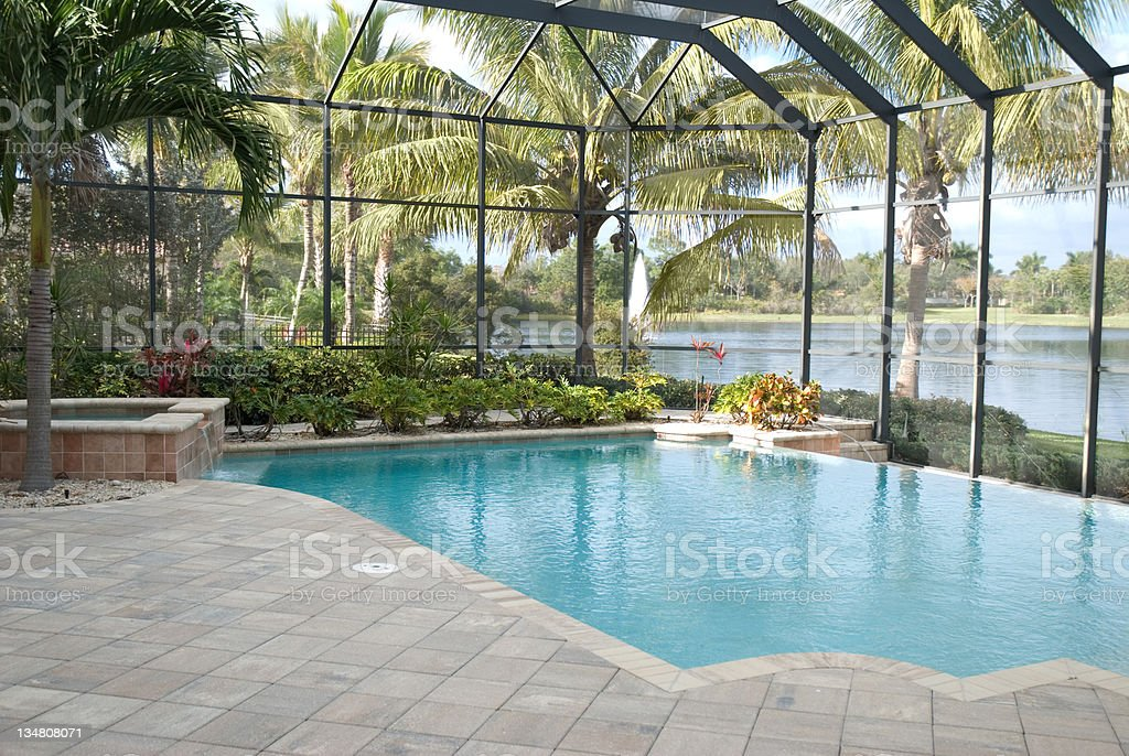 A backyard pool located in a tropical setting covered by a screen...