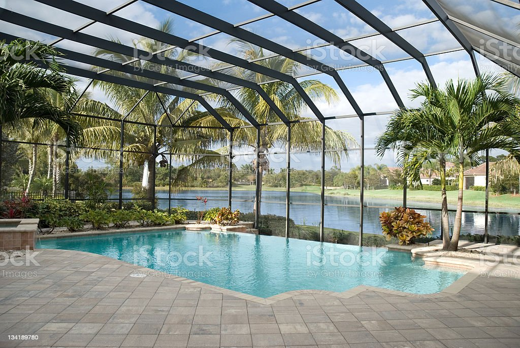 Backyard pool with window panel and ceiling next to lake stock photo