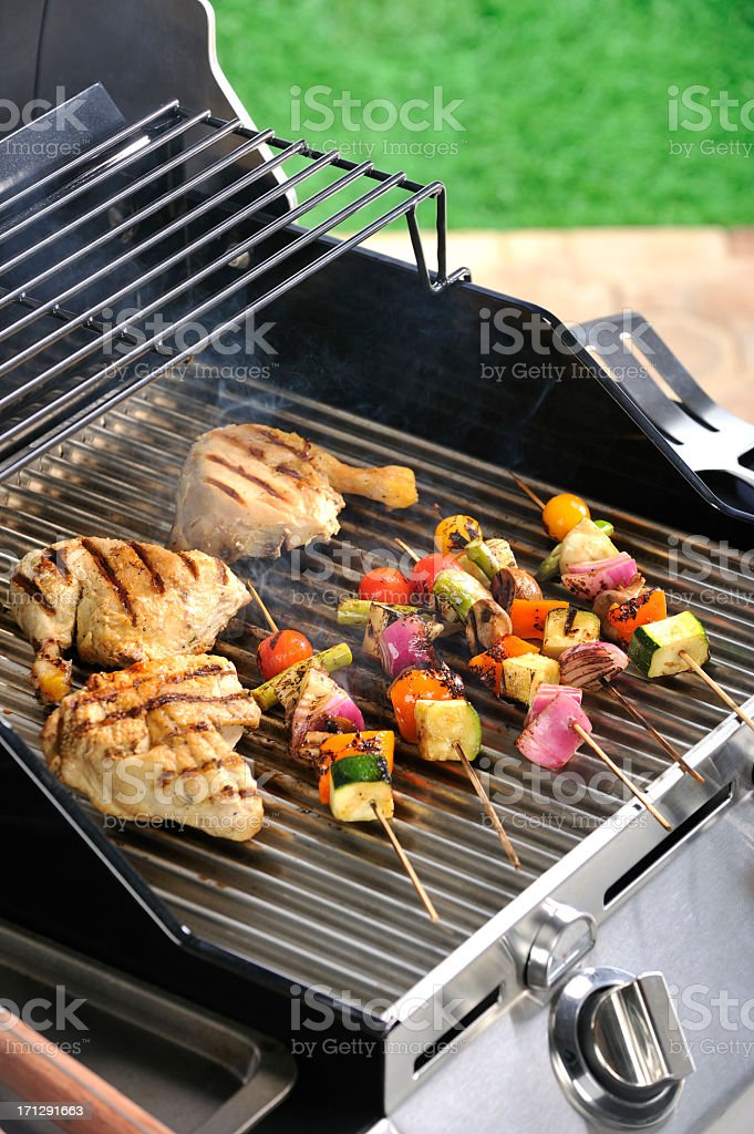 Backyard Summer barbecue grill with smoking grilled chicken & kabobs stock photo