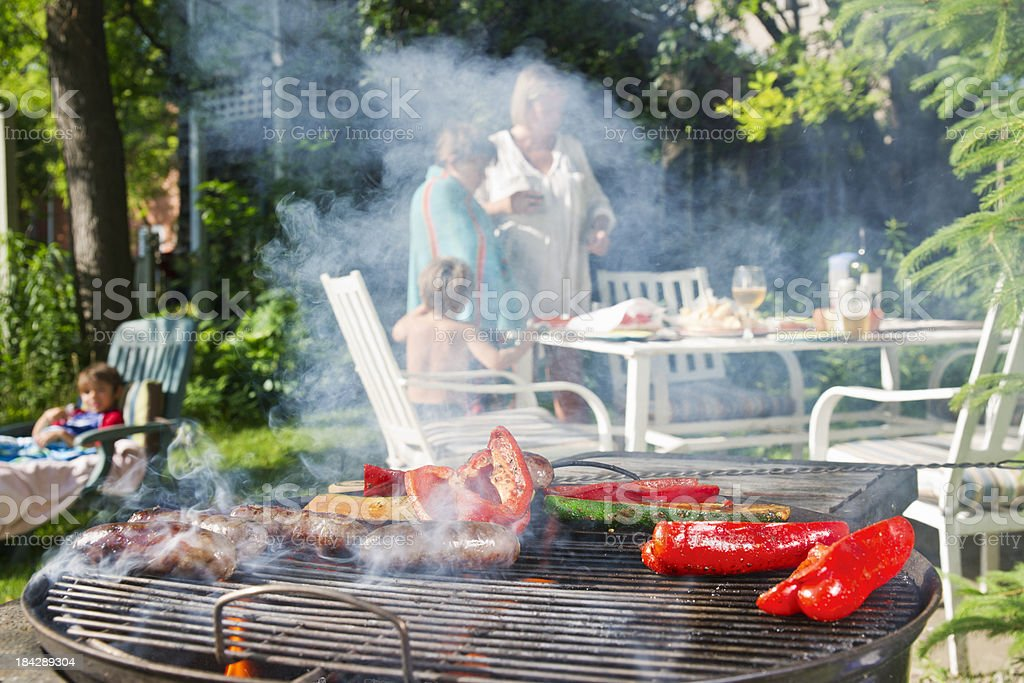A family enjoying a backyard BBQ with sausages and vegetables on the...
