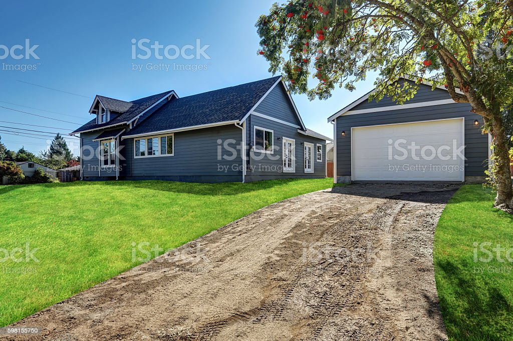 Backyard view of  blue siding house with detached garage stock photo