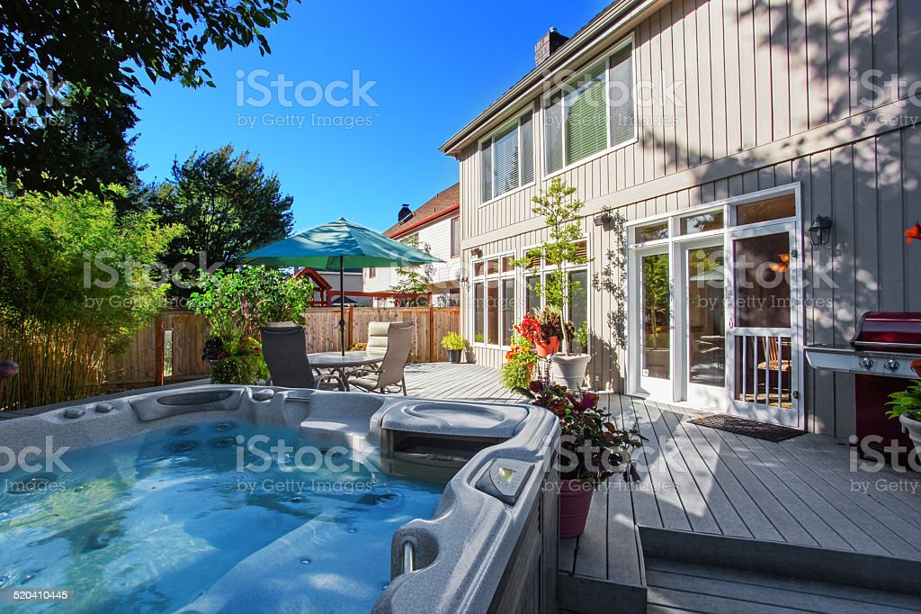Backyard with jacuzzi and patio area stock photo