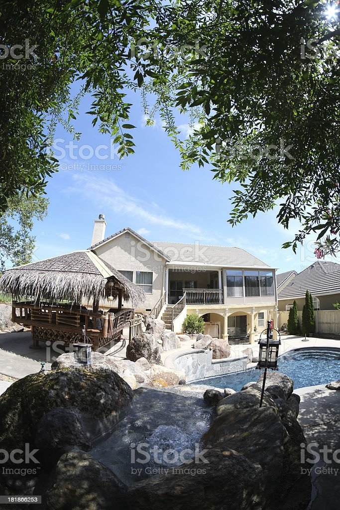 Backyard with Swimming Pool and Waterfall royalty-free stock photo