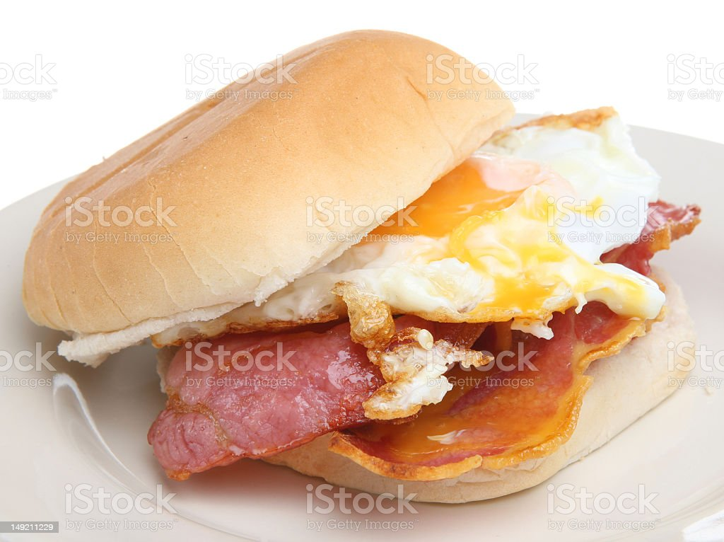 A bacon and egg breakfast sandwich on a white plate royalty-free stock photo