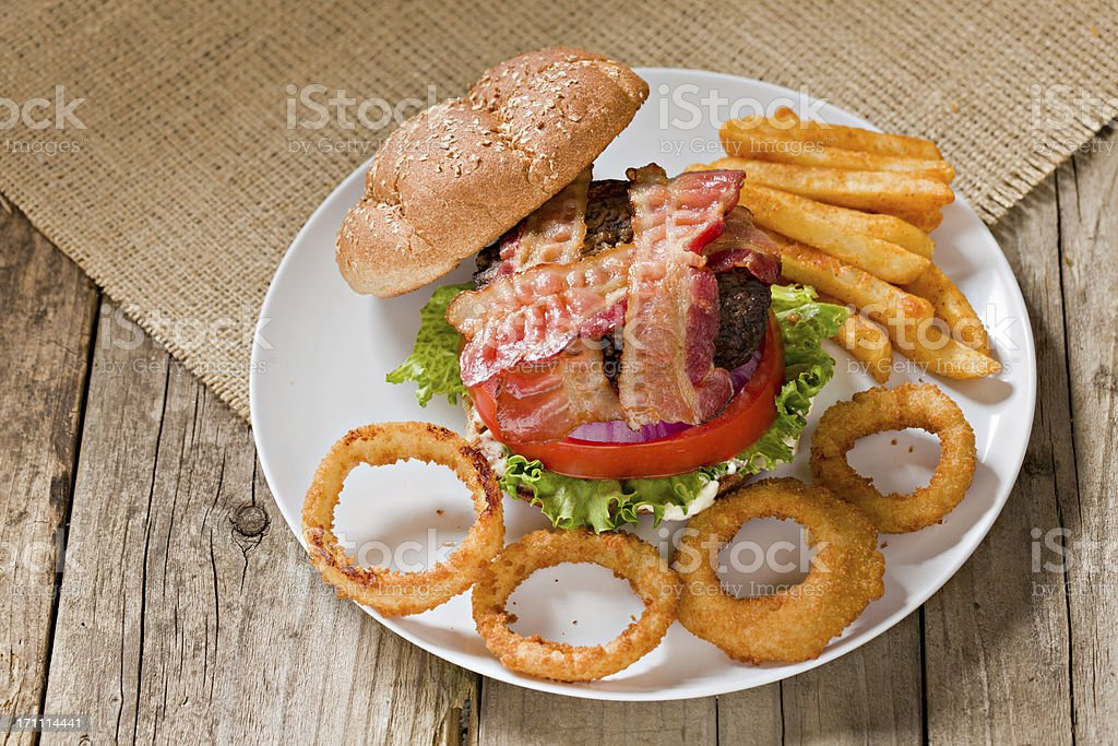 Bacon Burger, Onion Rings And Fries royalty-free stock photo