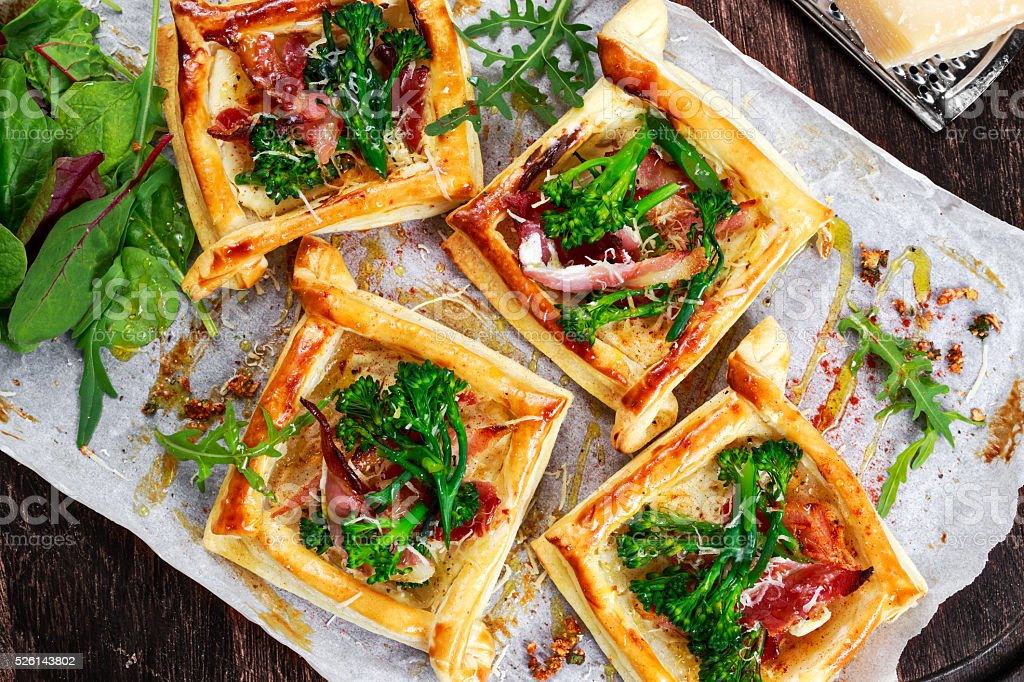 Bacon, cheese, tenderstem broccoli tips puff pastry, with green salad. stock photo