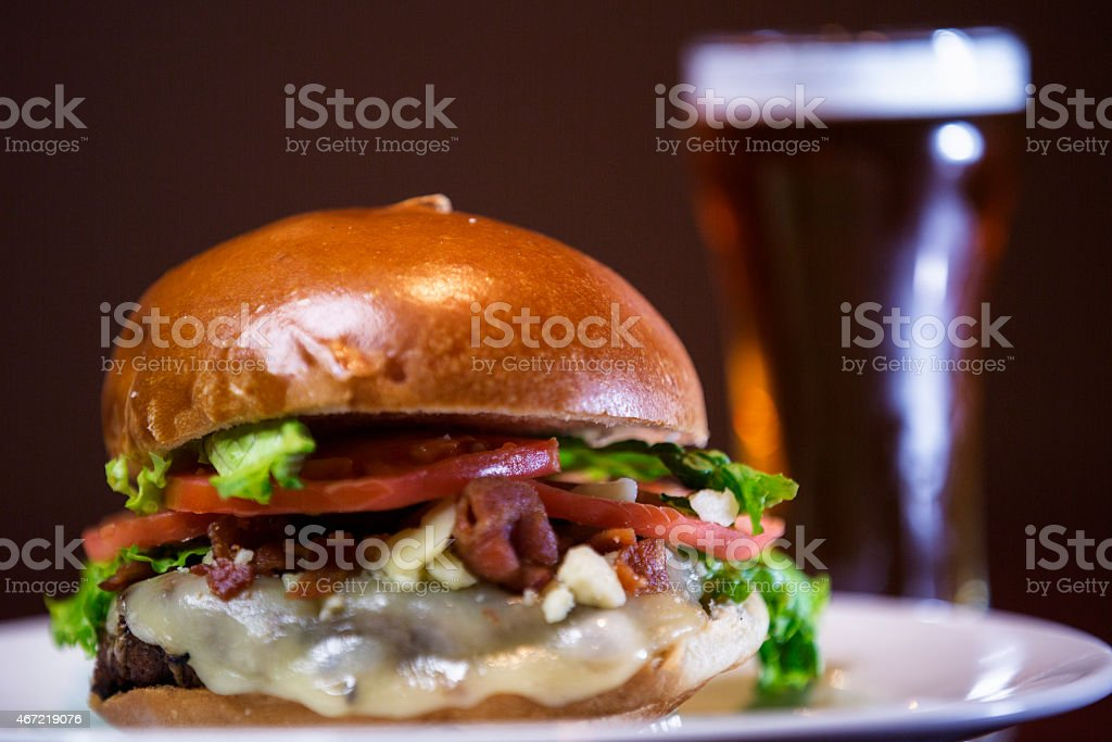 Bacon cheeseburger and a draft beer . stock photo