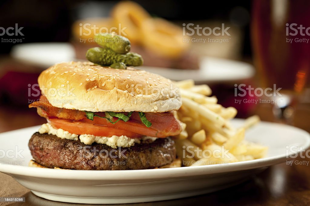 Bacon Cheeseburger with french fries served in restaurant royalty-free stock photo