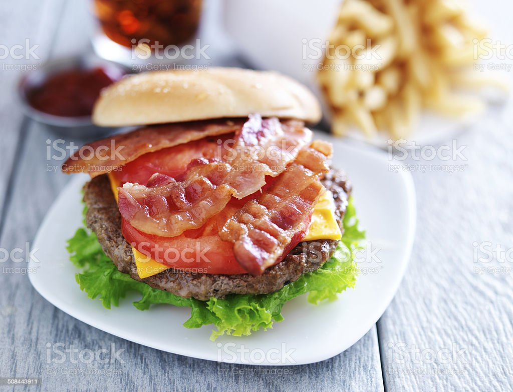bacon chesseburger with fries and cola stock photo