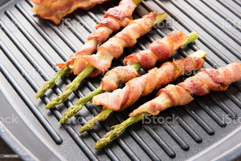 Bacon slice and asparagus wrapped in bacon being cooked stock photo