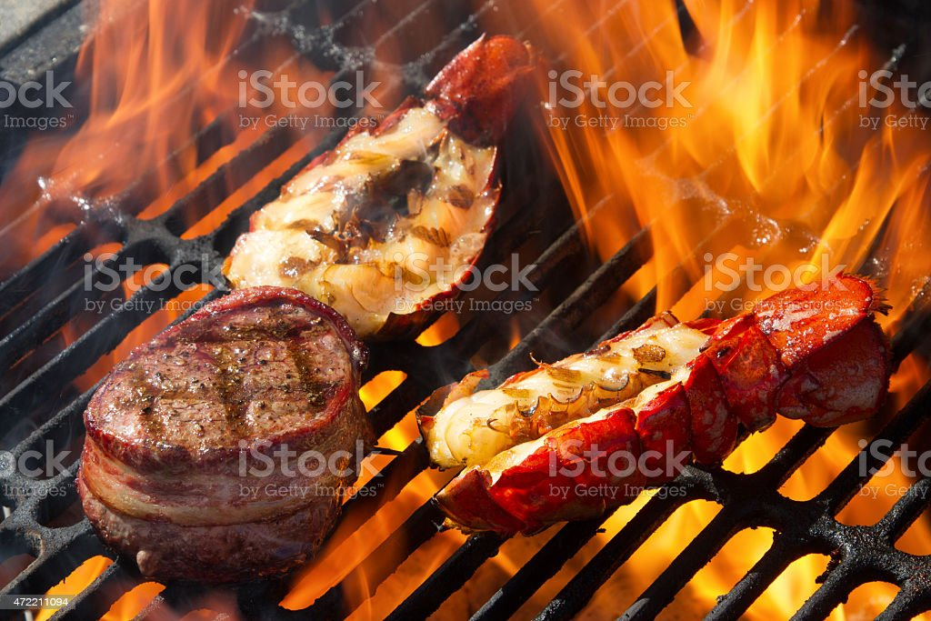 Bacon Wrapped Beef Filet Mignon and Grilled Lobster Tails, Flame stock photo