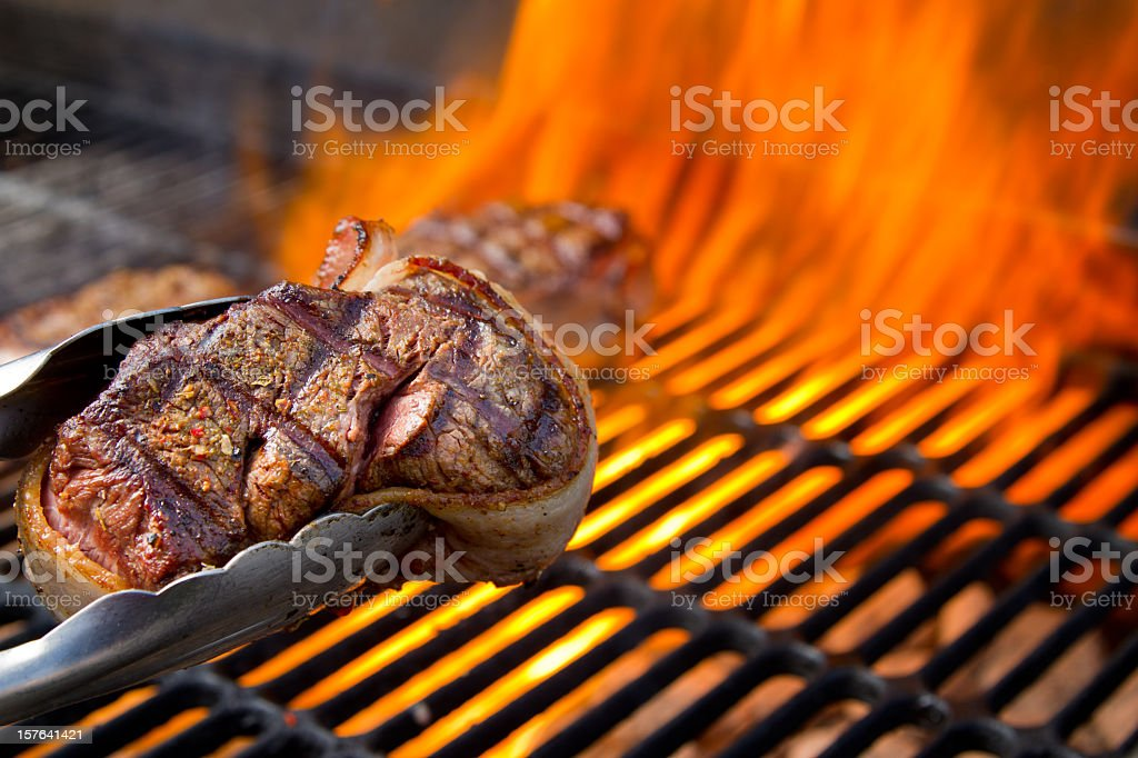 Bacon Wrapped Beef Filet Mignon on Grill with Dancing Flames stock photo