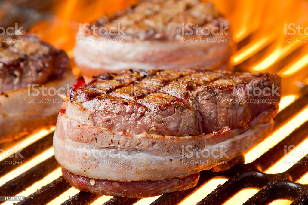 Bacon Wrapped Filet Mignon on Grill with Fire royalty-free stock photo