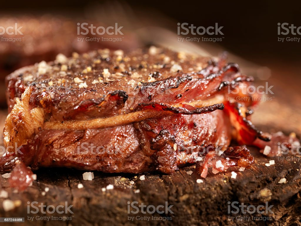 Bacon Wrapped Medium Rare Steak Fillets Sautéed in Garlic Butter stock photo