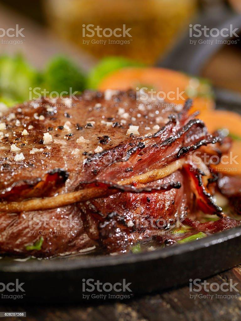 Bacon Wrapped Steak Fillets Sautéed in Garlic Butter stock photo
