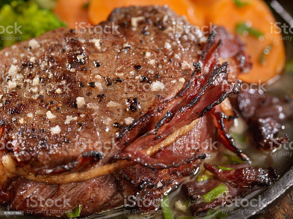 Bacon Wrapped Steak Fillets Sautéed in Garlic Butter stock photo