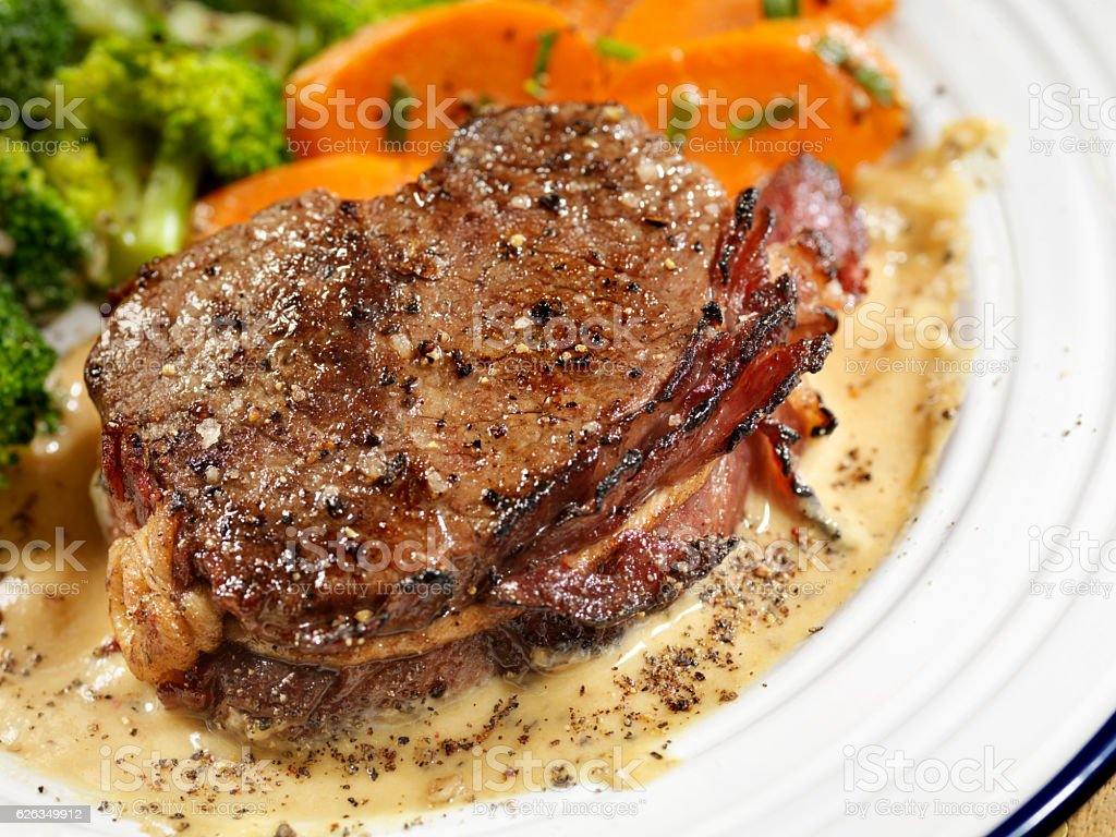 Bacon Wrapped Steak Fillets with a Cream Peppercorn Sauce stock photo