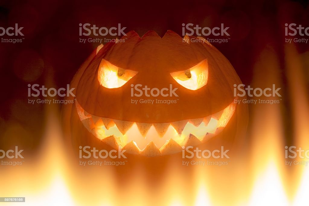 Bad carved halloween pumpkin in hot burning hell fire flames stock photo