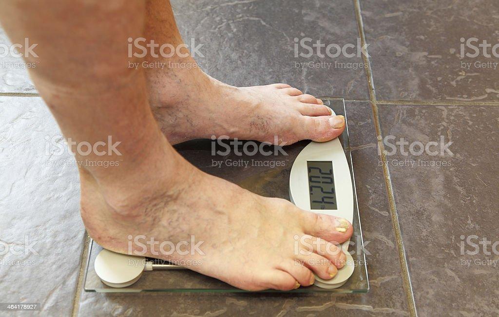 bad feet on bathroom scales stock photo