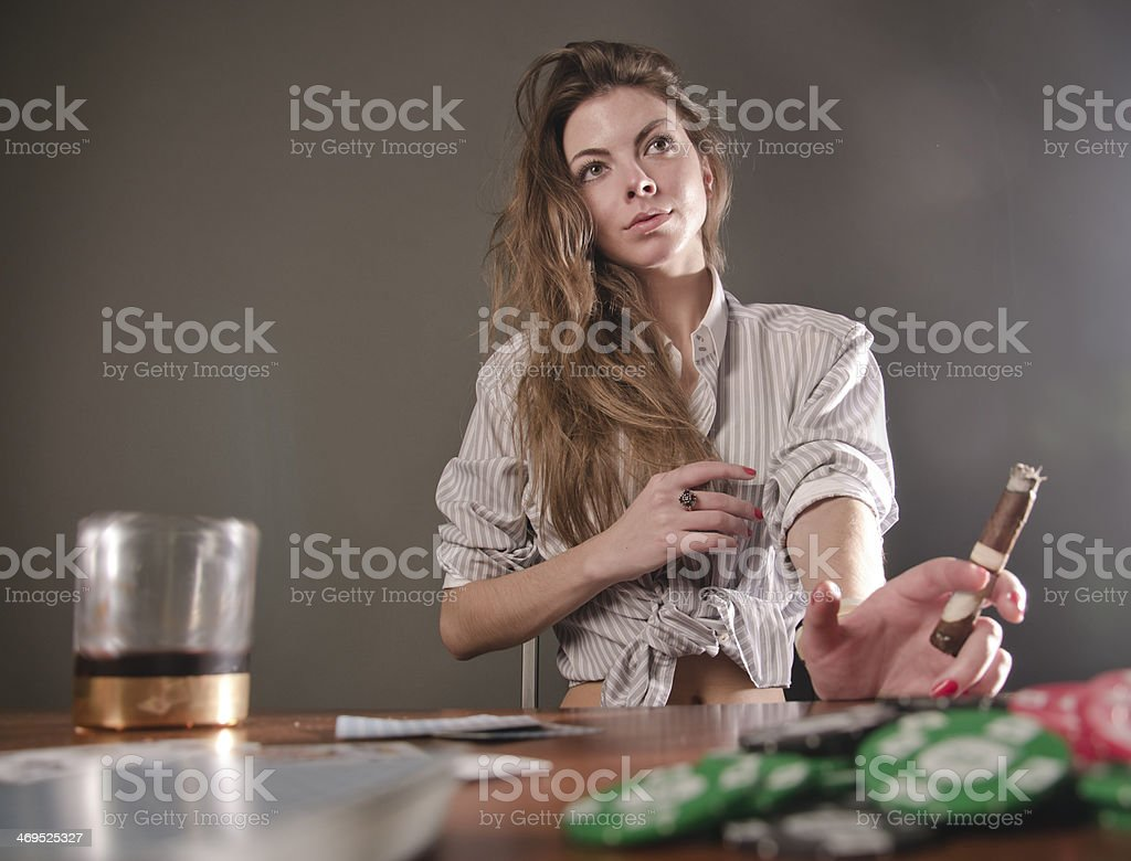 Bad girl plays poker with whiskey and cigar stock photo