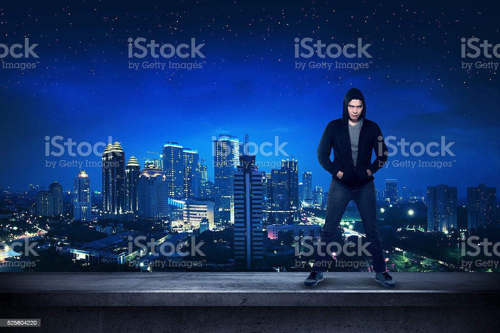 Bad guy standing on the building rooftop stock photo