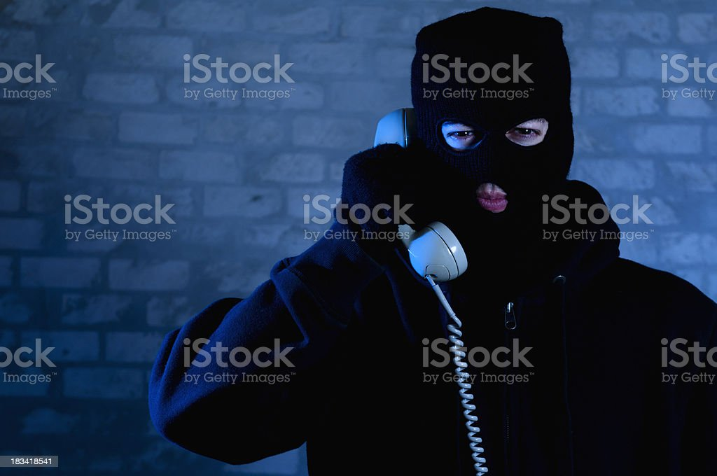 Bad guy with mask is on the phone royalty-free stock photo